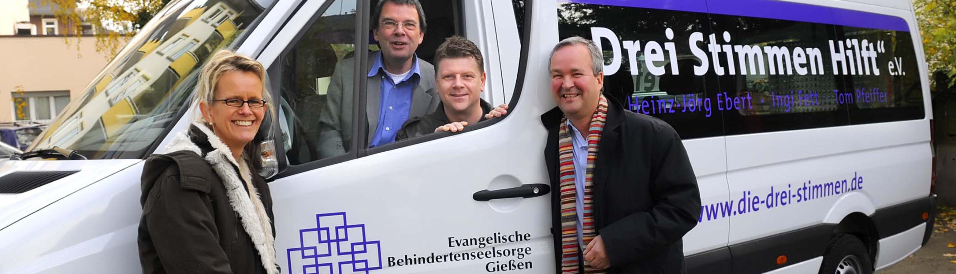 Die Drei Stimmen: Ingi Fett, Heinz-Jörg Ebert und Tom Pfeiffer gemeinsam mit Pfarrer Armin Gissel vor dem drei Stimmen hilft Bus.